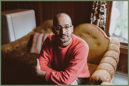 Oregon poet laureate Anis Mojgani seated on caramel colored couch wearing a coral colored shirt