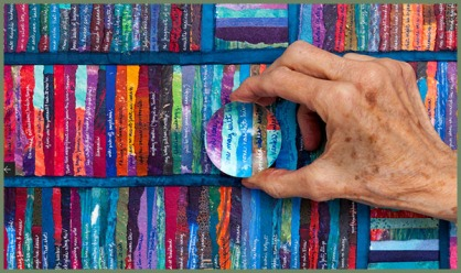 hand holding magnifying lens over colorful strips of paper with handwritten poetry text