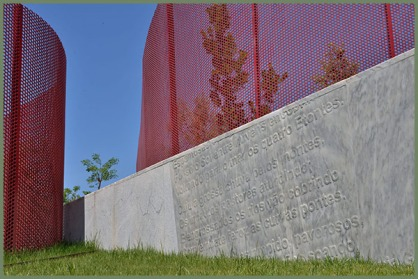a sloped marble wall embossed with part of a poem in Portuguese and flanked by two large, red, curved and perforated fences